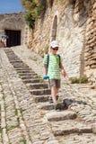 El muchacho está caminando abajo de los pasos de piedra Foto de archivo