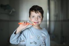 El muchacho está cepillando sus dientes imagenes de archivo