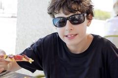El muchacho está comiendo la pizza Fotos de archivo libres de regalías