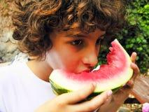 El muchacho está comiendo la rebanada de la sandía Foto de archivo libre de regalías