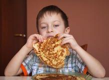 El muchacho está comiendo las crepes sabrosas Fotos de archivo libres de regalías