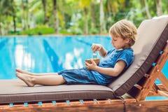 El muchacho está comiendo los cubos del mango en el fondo de la piscina fotografía de archivo