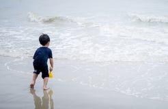 El muchacho está corriendo abajo al océano Imágenes de archivo libres de regalías