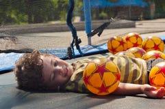 El muchacho está descansando sobre el trampolín Foto de archivo libre de regalías
