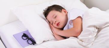 El muchacho está durmiendo en una cama blanca, al lado de la almohada es un libro con los vidrios Foto de archivo