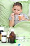 El muchacho está enfermo. Sosteniendo una píldora y no quiera beberla Foto de archivo