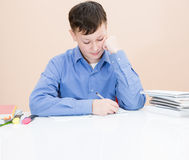 El muchacho está escribiendo en un cuaderno en la tabla Fotos de archivo libres de regalías