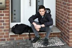El muchacho está esperando alguien con llave de la puerta principal Foto de archivo libre de regalías