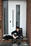 El muchacho está esperando alguien con llave de la puerta principal Foto de archivo