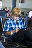 El muchacho está esperando salida en el aeropuerto Fotografía de archivo libre de regalías