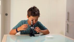 El muchacho está estudiando una diapositiva del microscopio almacen de video