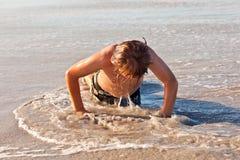 El muchacho está haciendo pectorales en la playa Fotografía de archivo