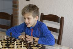 El muchacho está jugando a ajedrez fotografía de archivo