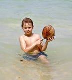 El muchacho está jugando con un coco en una playa Imagenes de archivo