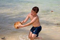 El muchacho está jugando con un coco en una playa hermosa Imagenes de archivo