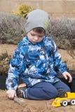 El muchacho está jugando con un excavador del amarillo del juguete en el jardín Fotos de archivo