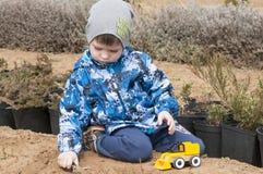 El muchacho está jugando con un excavador del amarillo del juguete en el jardín Imágenes de archivo libres de regalías