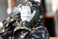 el muchacho está jugando Paintball en el campo dos equipos de jugadores de Paintball en forma del camuflaje con las máscaras, cas fotos de archivo