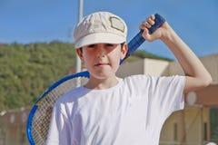 El muchacho está jugando a tenis Imágenes de archivo libres de regalías