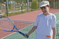 El muchacho está jugando a tenis Imagen de archivo