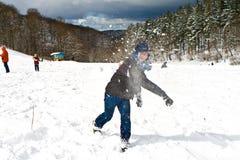 El muchacho está lanzando una bola de nieve en paisaje hivernal Fotografía de archivo libre de regalías