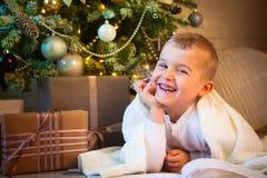 El muchacho está leyendo un libro que miente cerca del árbol de navidad Foto de archivo libre de regalías