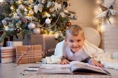 El muchacho está leyendo un libro que miente cerca del árbol de navidad Fotos de archivo