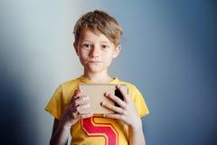 El muchacho está llevando a cabo realidad virtual googlea, VR, fondo azul Imagenes de archivo