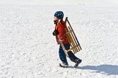 El muchacho está llevando su trineo largo en paisaje hivernal Imágenes de archivo libres de regalías