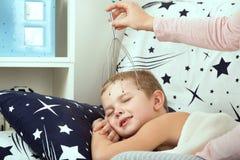 El muchacho está mintiendo en la cama, mamá lo está haciendo un masaje principal Imagen de archivo