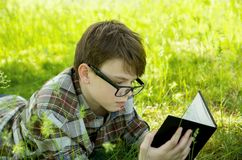 El muchacho está mintiendo en la hierba verde en el parque y está leyendo un libro Relájese, al aire libre Imagenes de archivo
