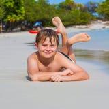 El muchacho está mintiendo en la playa Foto de archivo libre de regalías
