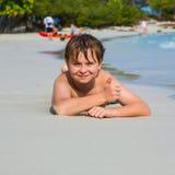 El muchacho está mintiendo en la playa Imagenes de archivo