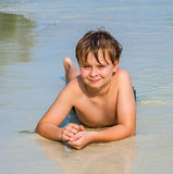 El muchacho está mintiendo en la playa Fotos de archivo libres de regalías