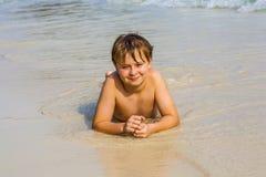 El muchacho está mintiendo en la playa y disfruta del agua y del uno mismo de la mirada Imagenes de archivo