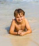 El muchacho está mintiendo en la playa y disfruta del agua y del uno mismo de la mirada Imagen de archivo libre de regalías