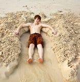 El muchacho está mintiendo en una cama arenosa en la playa del ful del beauti Foto de archivo