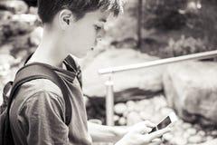 El muchacho está mirando en un teléfono elegante Foto de archivo