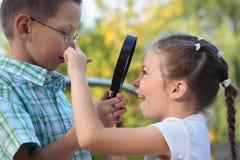 El muchacho está mirando a la muchacha alegre a través de la lupa Imagenes de archivo