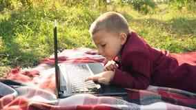 El muchacho está mirando el ordenador almacen de metraje de vídeo