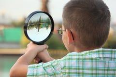 El muchacho está mirando a través de la lupa en parque de la caída Imagen de archivo libre de regalías