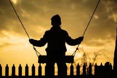 El muchacho está montando en un oscilación en la puesta del sol Foto de archivo