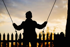 El muchacho está montando en un oscilación en la puesta del sol Fotografía de archivo libre de regalías