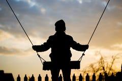 El muchacho está montando en un oscilación en la puesta del sol Imagen de archivo libre de regalías