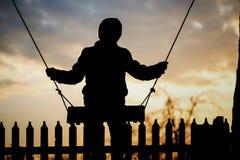 El muchacho está montando en un oscilación en la puesta del sol Fotos de archivo libres de regalías