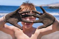 El muchacho está mostrando las manos en la arena. Imágenes de archivo libres de regalías