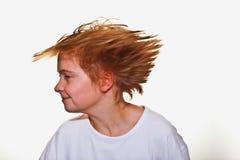El muchacho está moviendo su cabeza y los pelos están volando Foto de archivo