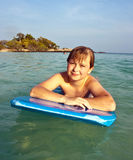 El muchacho está nadando en su tabla hawaiana Fotografía de archivo