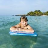 El muchacho está nadando en su tabla hawaiana Imágenes de archivo libres de regalías