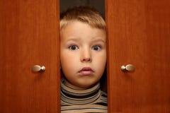 El muchacho está ocultando en guardarropa Imagen de archivo
